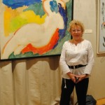 художник Ирина Покладова на фоне работы Валерия Волкова